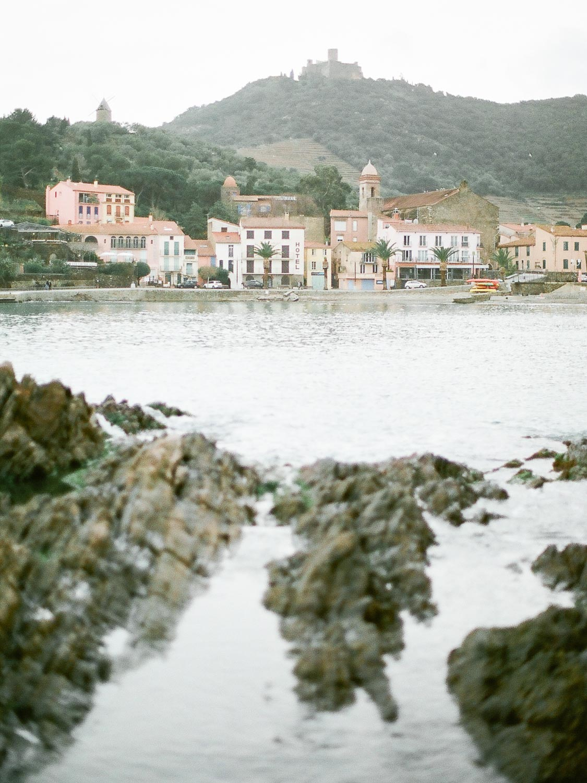 la ville de collioure avec premier plan de mer flou et rochers